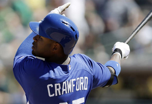 Dodgers outfielder Carl Crawford hits a solo home run against the Oakland Athletics during a spring training game.