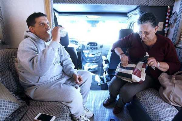Ara Manoogian takes a drink of water with his mom, Sylva Manoogian, in his RV on Monday.