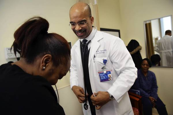 Dr. Clyde Yancy, chief of cardiology at Northwestern University's Feinberg School of Medicine, walks with patient Tiffany Hendricks, 29. Yancy said what patients need most is coaching and support that can help them make lasting behavioral changes, but that's no easy task.