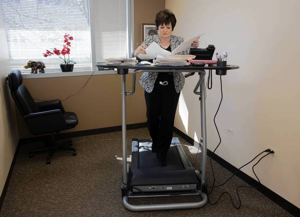 """Sheree Lipkis, of Northbrook, installed a treadmill desk in her office so she can walk while she checks emails and lab results between patients. """"I'm really not a gym person,"""" she says."""