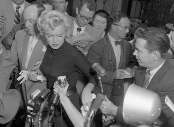 Reporters hounding Marilyn Monroe and attorney Jerry Giesler outside of her home in Los Angeles in 1954 after Joe DiMaggio moved out.