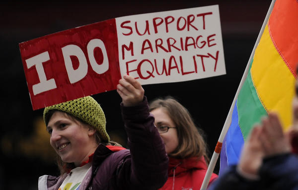 Heather Sinclair holds a sign in support of gay rights and marriage during a rally on the eve of Supreme Court arguments about the issue in Hartford on Monday.