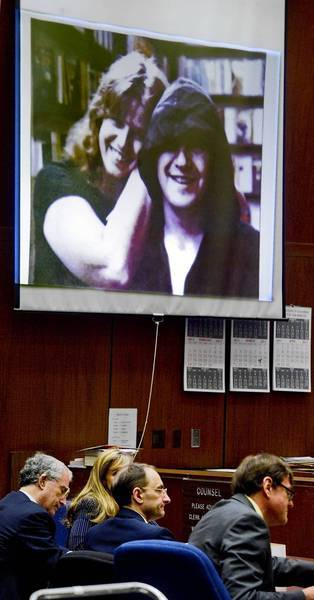 "Christian Karl Gerhartsreiter, center, sits with his lawyers as a photo of Linda and John Sohus is projected onto a screen in the downtown L.A. courtroom where his murder trial is taking place. Susan Coffman, a close friend of Linda, described the Sohuses as ""two contented puppies"" who were ""happy to be in each other's presence."""