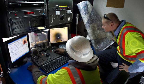 Newport News city workers Charles Stone and Joshua Black use video equipment in their truck to look for damage in sewer pipe.