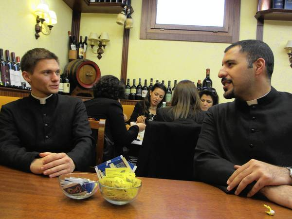 Seminarians Chris Kerzich, 29, left, and Khalil Hattar, 25, relax in a Rome cafe after serving as ushers during the inauguration Mass of Pope Francis in nearby St. Peter's Square on March 19.