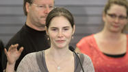 In this photo from October 2011, Amanda Knox waves to supporters after arriving in Seattle following her acquittal of the murder of roommate Meredith Kercher and her release from prison in Italy.