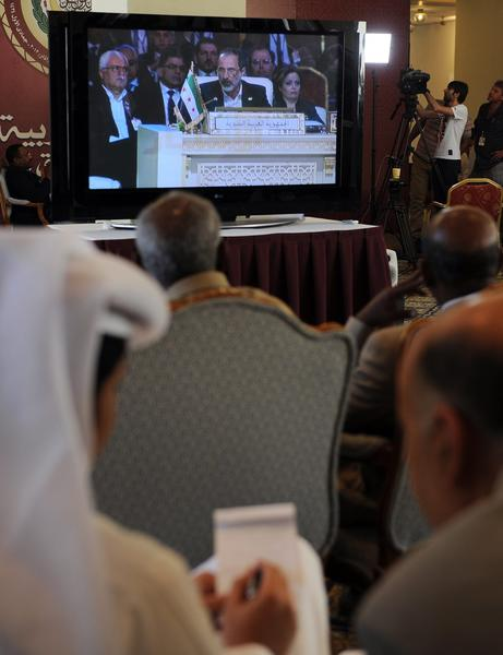 Members of the news media watch a live video feed of Syrian opposition leader Moaz Khatib speaking to the opening session of the Arab League summit in Doha, Qatar, on Tuesday. The Syrian opposition was handed Syria's seat in the Arab League.