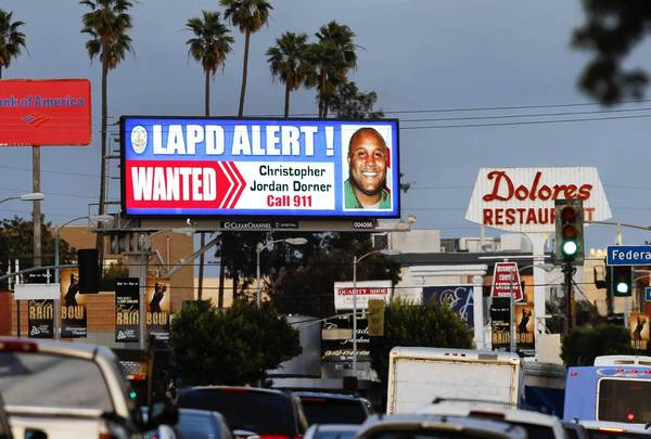 "A digital billboard along Santa Monica Boulevard displays a ""wanted"" alert for former Los Angeles police officer Christopher Dorner"