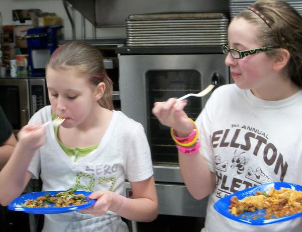 Taylor Myroniuk (left) and Jasmine Wiatrolik enjoy eating the broccoli rabe dish they helped create in the Pellston Middle School 21st Century class.