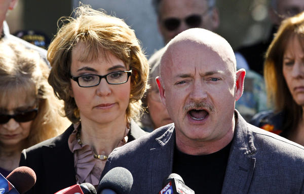 Former Rep. Gabrielle Giffords stands beside her husband, former astronaut Mark Kelly, during a return to the supermarket where she was wounded in a shooting rampage two years ago in Tucson, Ariz.