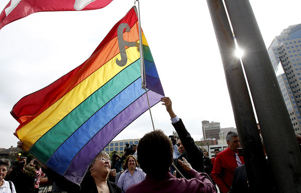 Supporters of same-sex marriage raise an LGBT pride flag over the Long Beach Civic Center on Tuesday. The flag will remain flying for the two days that the Supreme Court hears gay rights-related cases.