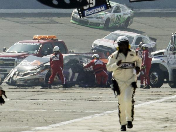 Rescue workers tend to the wreckage of the No. 11 FedEx Express Toyota driven by Denny Hamlin after he collided with Joey Logano on the final lap of the NASCAR Sprint Cup series auto race in Fontana on Sunday.