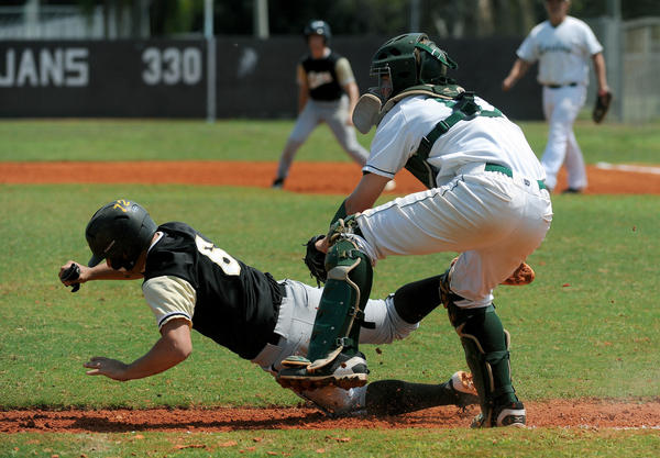 Atlantic High catcher Brad Myott tags out Olympic Heights Vinnie Scambone on a failed suicide squeeze.