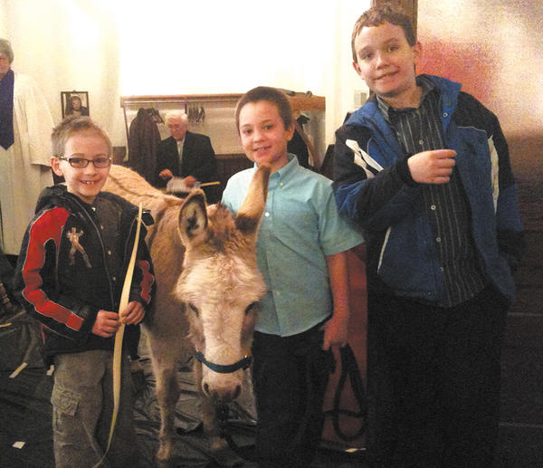Caroline the Donkey, shown with, from left, Jackson Mollo, Jack Martin and Joe Mollo led the processional for the Palm Sunday service at Washington Square United Methodist Church in Hagerstown.