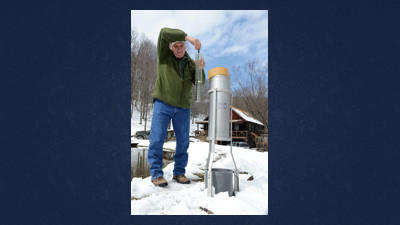 A.J. Jarosz, Glencoe, demonstrates how he uses a National Weather Service rain gauge to measure precipitation. Jarosz said that he recorded 8.2 inches of snow during snowfall on Monday and Tuesday.