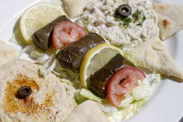 Tria's Trio is an appetizer prepared with babaganoush, grape leaves and hummus and served with pita bread.
