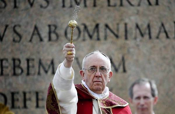 Pope Francis sprinkles holy water with an aspergillum as a blessing during the Palm Sunday mass at Saint Peter's Square at the Vatican.