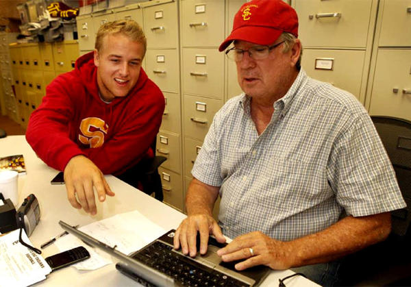 USC football quarterback Matt Barkley, left, teaches Los Angeles Times sports columnist T. J. Simers, how to set up and use a twitter account in August.