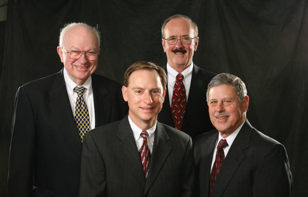 Front row, John R. Schnitzer, left, managing member of Smith Elliott Kearns & Co. LLC, and Ronald S. Kearns, who served in that position from 1989-99. Back row, Merle S. Elliott, left, managing member from 1963-89, and Edward L. Buchanan IV, who was in that post from 2000-09.