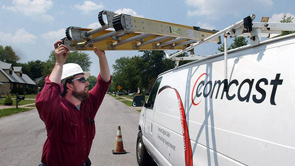Comcast communications technician, Chad Riggle, hoists a ladder onto his truck after a service call in Indianapolis, Indiana.