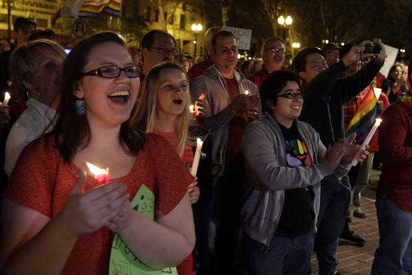 Jessica Christensen, left, celebrates with others during a candlelight vigil held by supporters of same-sex marriage at the Ronald Reagan Federal Building and U.S. Courthouse in Santa Ana.