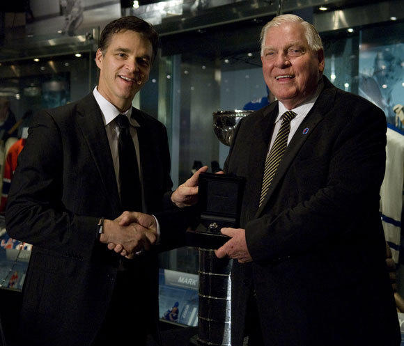 Luc Robitaille, left, hands his Stanley Cup ring to Hockey Hall of Fame Chairman Bill Hay.