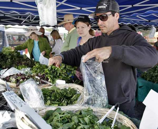 Carlo Micalizio and his wife Amy grab spinach and other greens at the La Cañada Flintridge Farmer's Market.