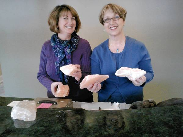 Karen Stoelinga, left, and Peggy McDonald hold chunks of pink salt that will line the cave at their new shop, Primal Oceans Salt Cave in La Grange.