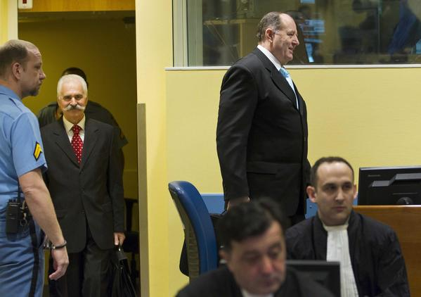 Former Bosnian Serb security official Stojan Zupljanin, second from the left, and former Bosnian Serb Interior Minister Mico Stanisic, standing at right, arrive in court in The Hague.