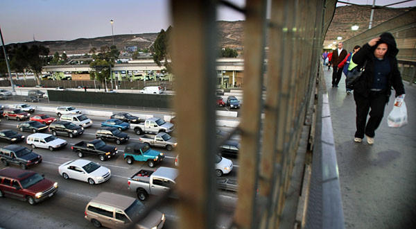 Traffic on I5 approaching the San Ysidro/Tijuana border gate clogs all southbound lanes. Shoppers and workers walk on an overpass leading to the pedestrian gate to Mexico.