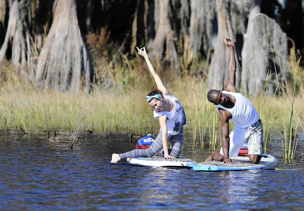 Taylor Names instructs Gary Daughtery during a Stand Up Paddleboard yoga class at Cypress COve Marina in Clermont.