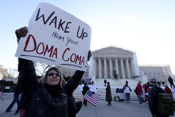 "Carolyn Marosy, a supporter of same-sex marriage rights, holds a sign that reads ""Wake Up From Your DOMA Coma"" outside the U.S. Supreme Court on the day the high court hears the case challenging the Defense of Marriage Act (DOMA) in Washington, D.C."