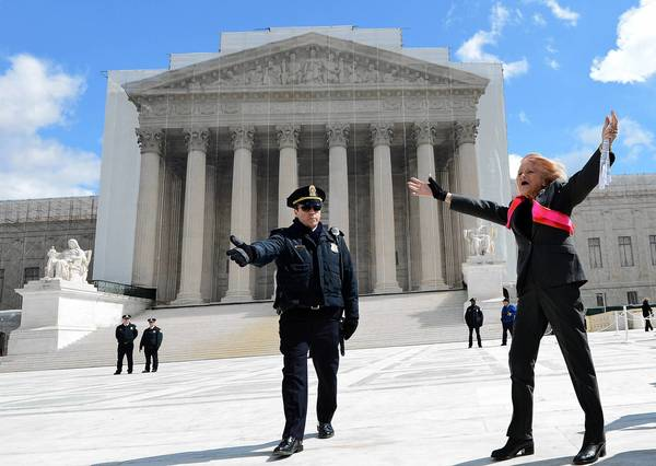 Edith Windsor, a lesbian widow whose case is being heard by the Supreme Court, gestures to supporters outside.