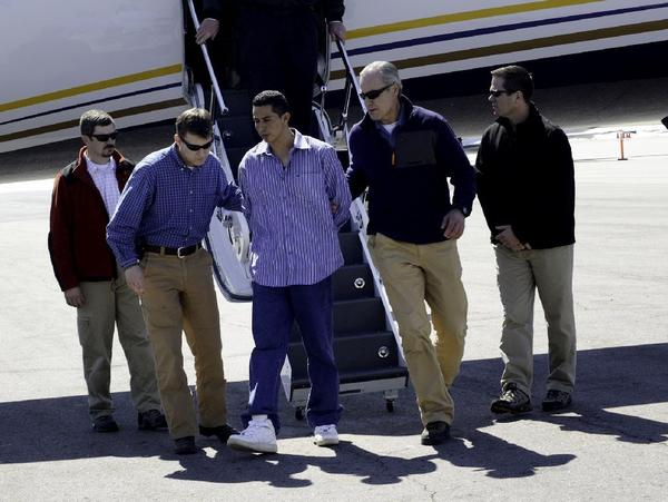 FBI agents escort Edwin Ernesto Rivera Gracias off a plane in Denver.