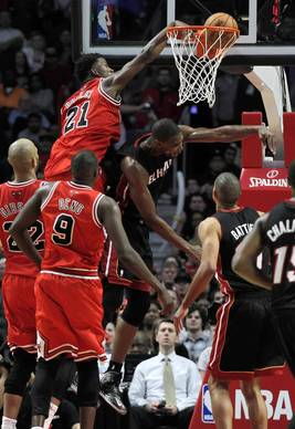 Jimmy Butler dunks over the Heat's Chris Bosh in the 3rd quarter.