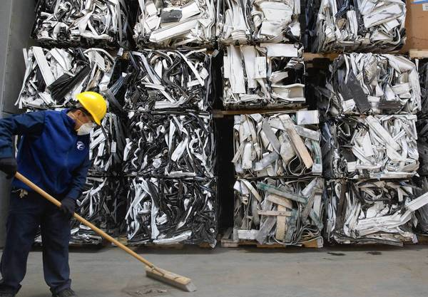 A worker sweeps Friday in front of bundles of window and door frames at a United Scrap Metal warehouse in Cicero.