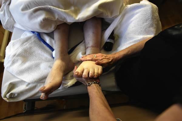 A massage therapist works on the feet of a terminally ill resident of the Hospice of Saint John on August 20, 2009 in Lakewood, Colorado.