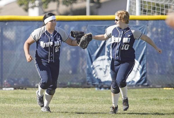 Newport Harbor High's Breanna Lopez, left, touches gloves with teammate Hope Noakes, right, after closing out an inning during a Battle of the Bay softball game against Corona del Mar on Wednesday.