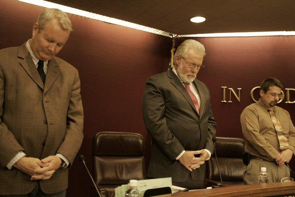 Lancaster Mayor Rex Parris (middle) prays at a city council meeting.
