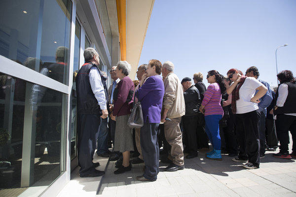 A security guard, left, watches as customers line up Thursday outside a Bank of Cyprus branch in Nicosia ahead of opening for the first time in two weeks.