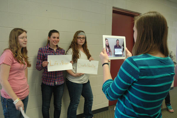 Sophomore Gabby Waterman videos classmates Taylor Ramage (from left), Allie Hodge and Lyndsay Towsley while making a public service announcement project for Karen Petersons 10-grade English class. The class is part of the one-to-one iPad initiative the Charlevoix school district started this year.