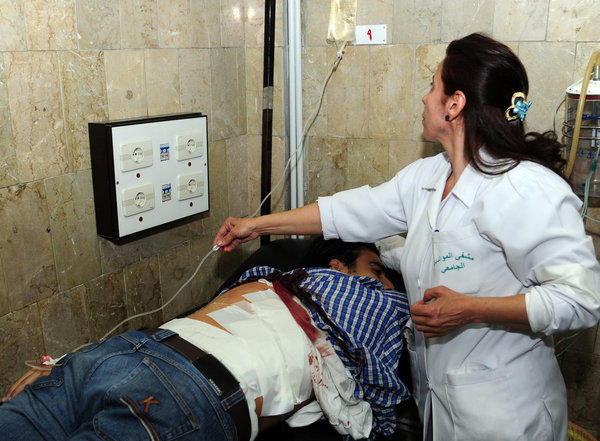 In this photo released by the Syrian official news agency SANA, a doctor treats an injured man who was wounded Thursday during a mortar strike on an open-air cafeteria at Damascus University.