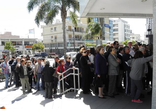 People wait in line outside the Laiki Bank branch in Limassol, Cyprus, on Thursday. All of the country's 26 banks were open for the first time in nearly two weeks, with restrictions on withdrawals.