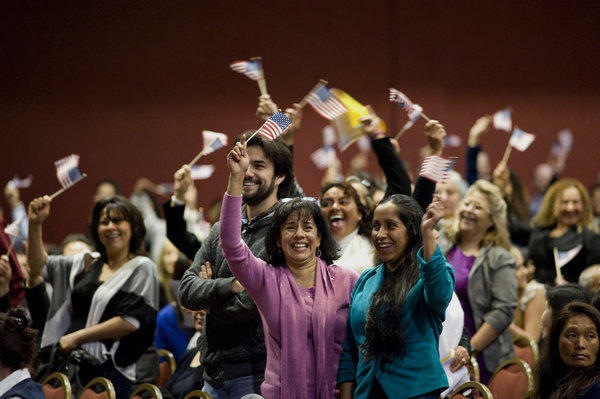 People from Mexico cheer and wave U.S. flags during a naturalization ceremony in San Diego.