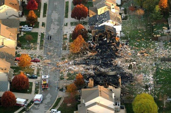 Two Indianapolis homes were leveled and numerous neighboring homes were damaged in a massive explosion that sparked a huge fire and killed two people.