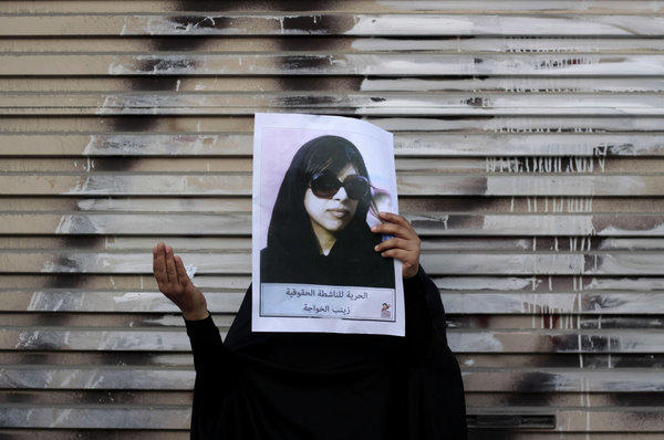 "An antigovernment protester holds up a picture of jailed opposition human rights activist Zainab Khawaja after a march in Malkiya, Bahrain. The sign reads, ""Freedom for rights activist Zainab Khawaja."""