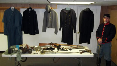 "The Rev. James Monticue stands by pieces from his Civil War collection which he will display and demonstrate in a program to be held April 9 ""Guns and Uniforms of the Civil War."""