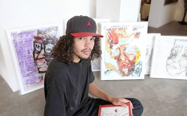 Julian St. John, an artist who has struggled with mental illness, sits among his most notable work that will be showcased at a one-night show at the Laguna Gallery of Contemporary Art.