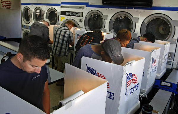 Voters huddle in the dryer section to mark their ballots at Super Suds laundromat polling place on Alamitos Avenue in Long Beach during the November 2012 election.