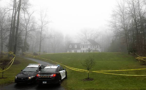 Police cordon off the home of Adam Lanza and his mother in December after the Newtown, Conn., school massacre. Search warrants show he had assembled an arsenal of guns, knives and ammunition.